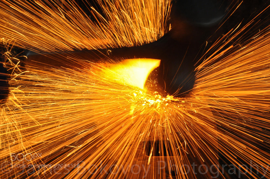Slag sparks fly through the air as a blacksmith shapes a piece of steel on the anvil.