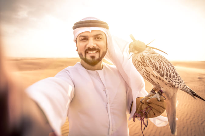 Arabic man with traditional emirates clothes walking in the dese
