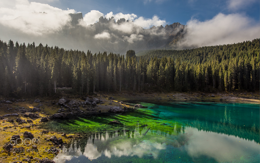 """<a href=""""http://www.hanskrusephotography.com/Workshops/Dolomites-October-7-11-2013/24503434_Pqw9qb#!i=2192063885&k=WVHrwWt&lb=1&s=A"""">See a larger version here</a>  This photo was taken during a photo workshop that I led in the Dolomites October 2012.  Lago di Carezza is well known for the beautiful surroundings with Rosengarten on one side and the Latemar behind the lake as seen in the photograph. The green water is quite amazing and a remarkable feature of this lake. It's a major tourist attraction in the area and sometimes it can be difficult to get the pictures you would like.   This is an HDR image blended from 5 exposures in the 32 bit Photomatix HDR plugin for Lightroom and then tone mapped in Lightroom 4.3."""