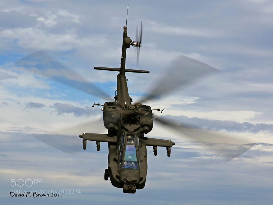 An AH-64D Apache, hence the title, dips its nose and picking up forward air speed.