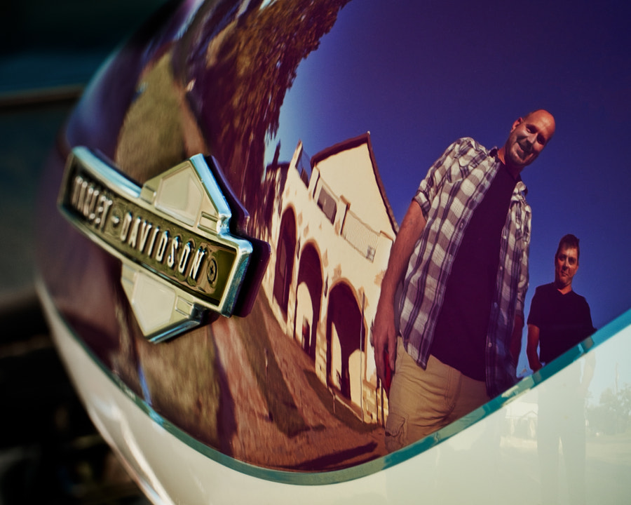 The reflection in the belly of a Harley of the winemaker, Tim, and the executive chef, Sean, at the Flat Creek Winery near Austin