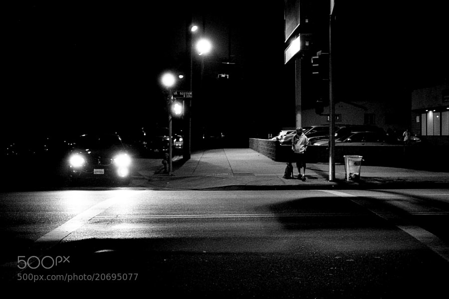 A man waits to cross the street on a dark night in LA