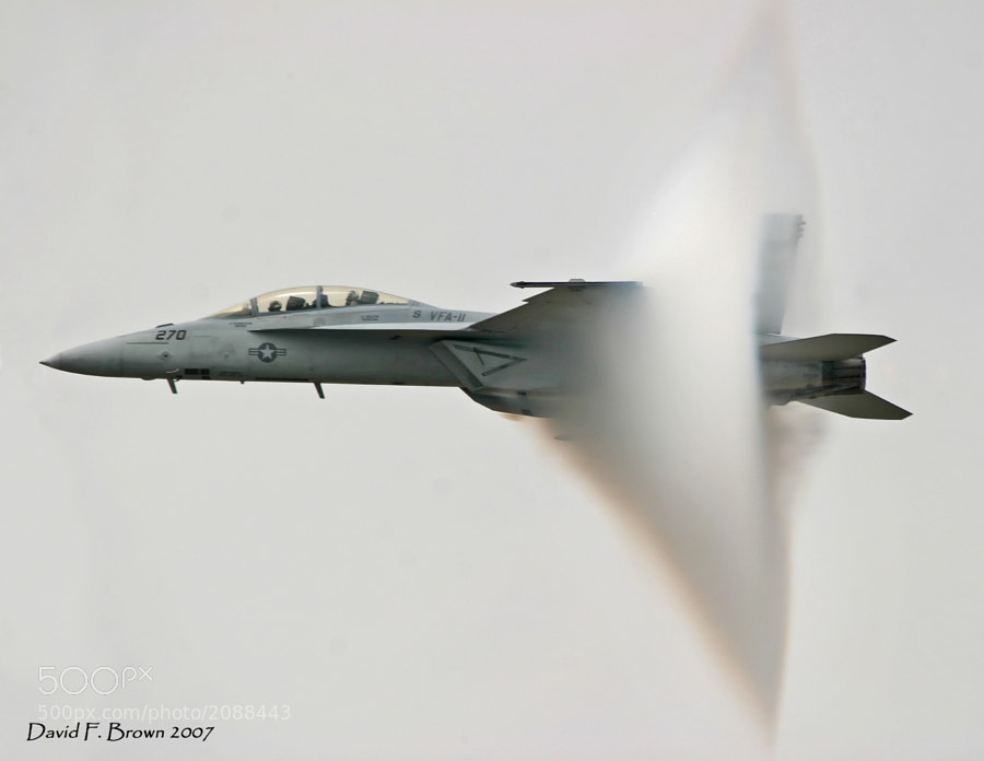 When people view this image they think the jet is breaking the sound barrier.  It was traveling very fast, but not at the speed of sound.  What you see here is a condensation cloud, better known in aviation circles as a 'vapor cone.'  Google or Bing the photo title for details.