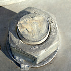 Large nut & bolt welded into cement.