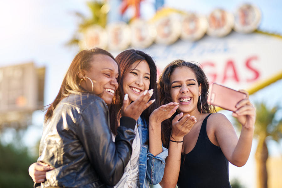all girl group of friends having fun taking selfies in front of welcome to las vegas sign by Joshua Resnick on 500px.com