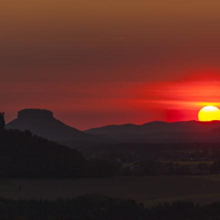 Sun behind hills