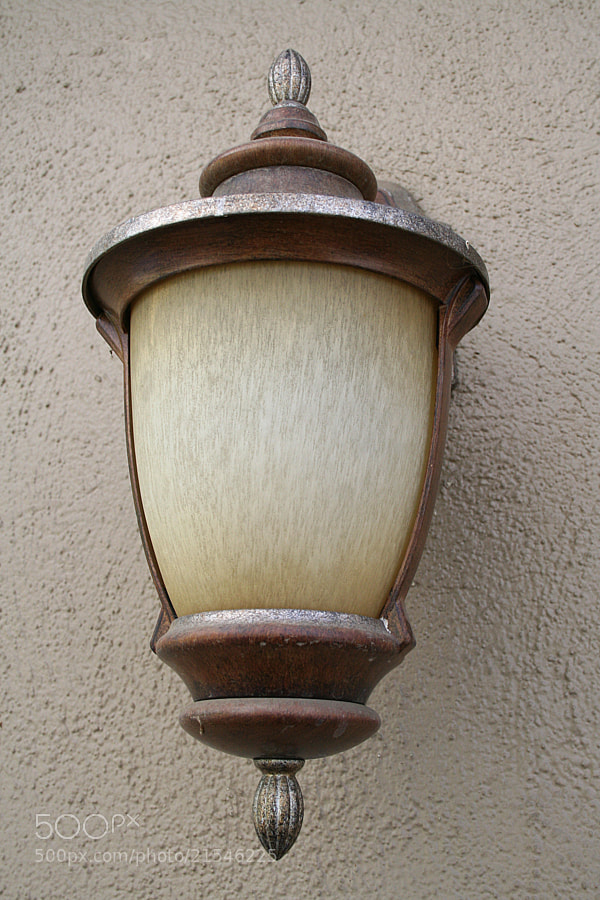 A brown sconce on a brown wall.