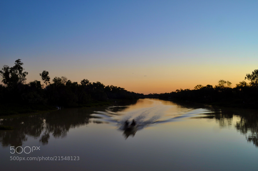 A boat cruises along the Thomson River at sunset