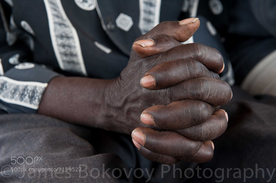 An elderly Zambian man folds his hands in prayer during a church service near Livingstone, Zambia