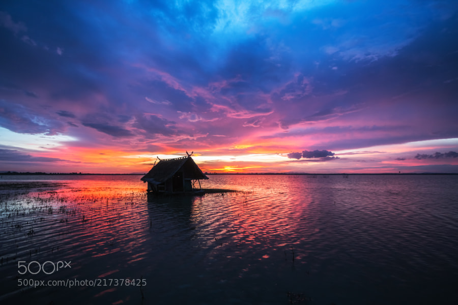 beautiful sunset with small hut on water surface