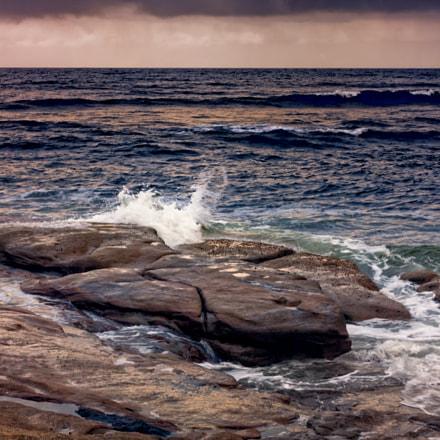 Waves Splash On The Rocks At Sunset