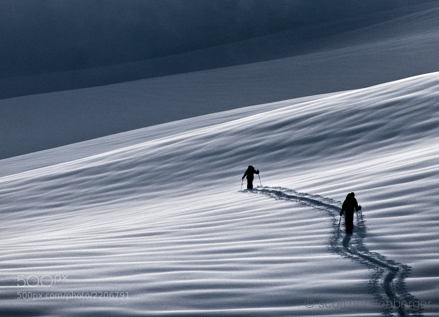 Two climbers make their way through fresh snow at dawn en route to the summit of Mt. Baker, Wahsington.