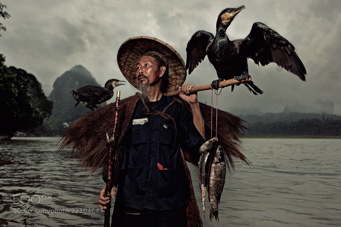 Photograph A Chinese fisherman with his two cormorants by Glenn Meling on 500px