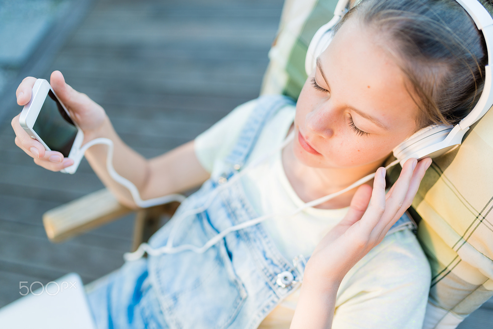 Closeup of pretty teen girl in headphones listening to music