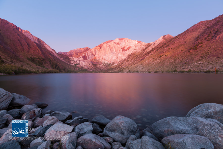 The warm glow of Laurel Mountain reflects off the smooth water of Convict Lake in California's Sierra Nevada.