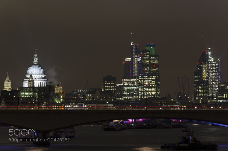 Night view from the Embankment (Hungerford Bridge) showing St Pauls Cathedral aside the modern buildings of Canary Wharf and the city