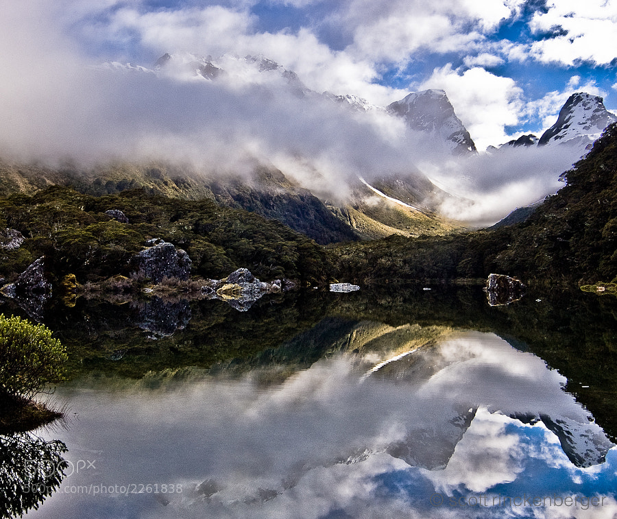An immense reflection on Mackenzie lake on the Routeburn Track multi day hike in the south island of New Zealand.