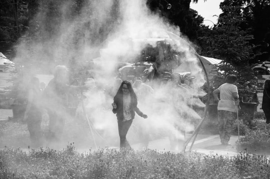 Girl passing through sprinkler water circle.