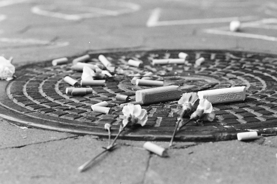 In black and white: various sizes of sidewalk chalk and a few carnations rest on a manhole cover situated within a public park.