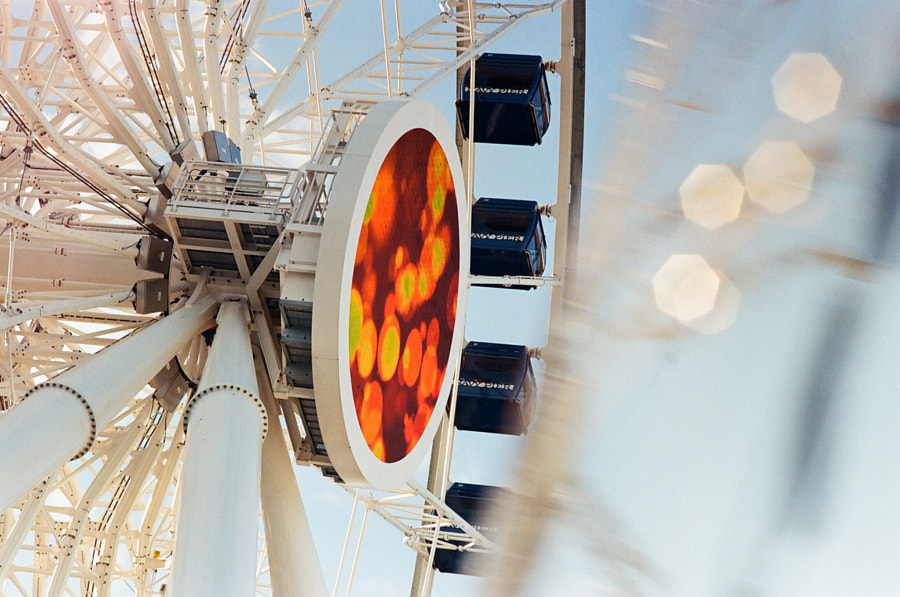 """Close-up of a spinning white Ferris wheel. Four deep blue cabins are adorned with the words """"Navy Pier"""". A large, circular LED screen is attached to the face of the Ferris wheel, displaying orange bokeh. There is photographic white bokeh and a motion blur in front of the scene."""