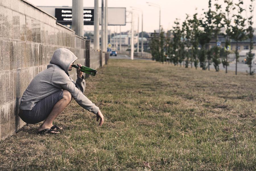 Алкоголик сидит на траве и пьет пиво из бутылки, автор — Лечение Наркомании на 500px.com