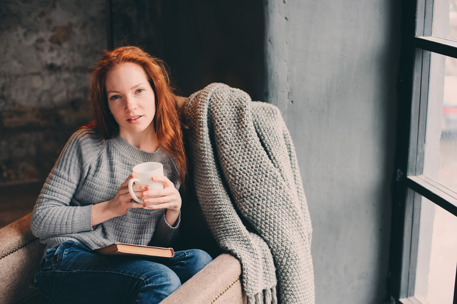 happy redhead woman relaxing at home in cozy winter or autumn weekend with book and cup of hot... by Maria Kovalevskaya on 500px.com