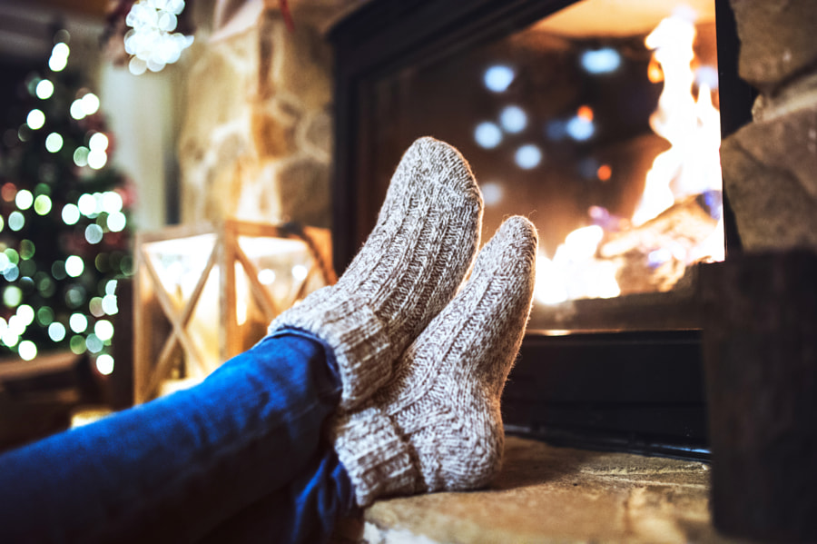 Feet of unrecognizable woman in front of the fireplace. by Jozef Polc on 500px.com