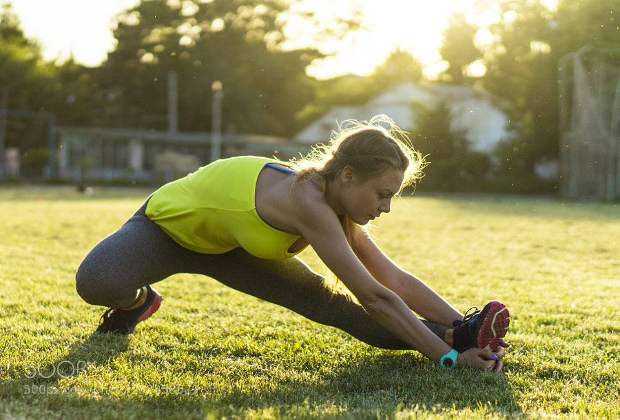 Runner woman stretching in stadium exercising outdoors fitness tracker wearable technology