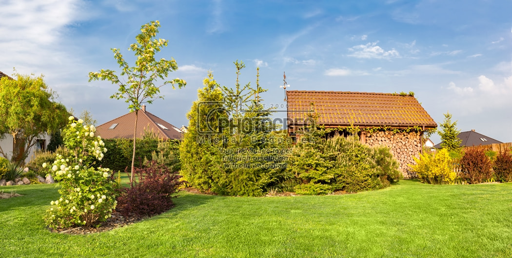 Backyard of a family house. Landscaped garden with green mown grass, wood shelter.
