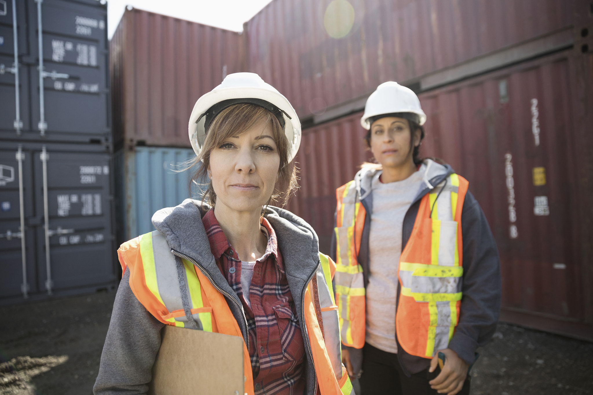 Portrait serious female workers in industrial container yard