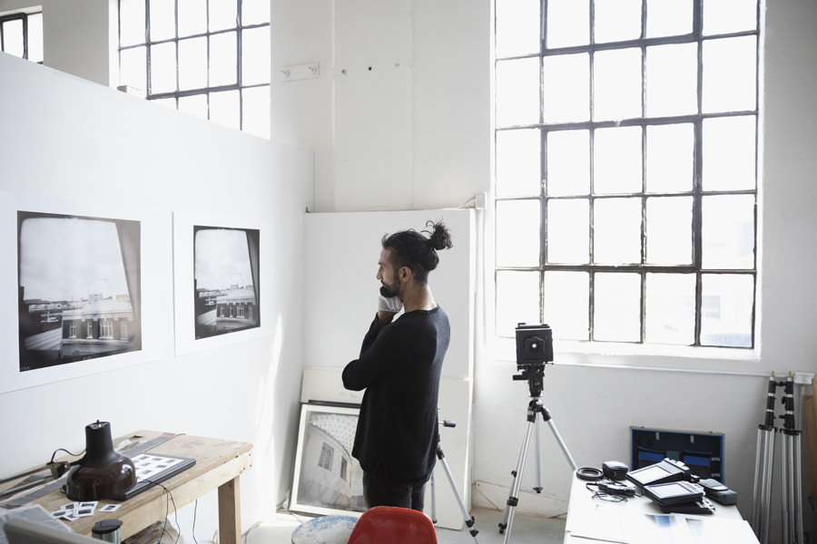Focused male photographer examining large photography print hanging on wall in art studio by Hero Images on 500px.com