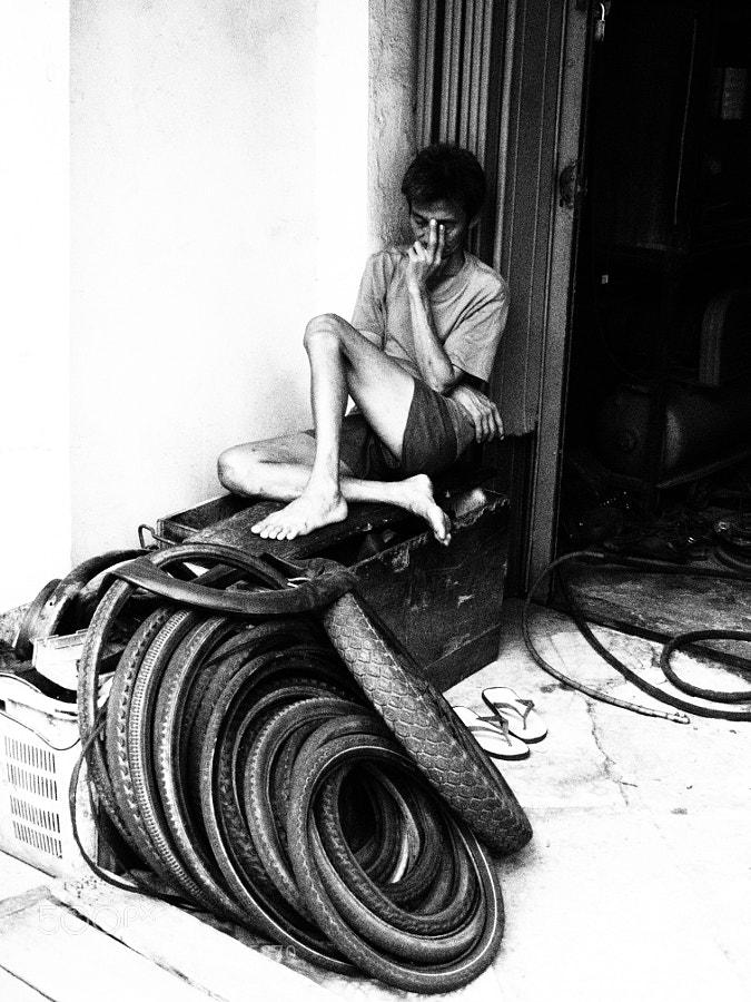 A tired mechanic taking a nab outside his workshop at Melaka, Malaysia.