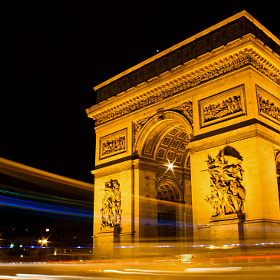 Arc de Triomphe in the center of Place de l'Etoile in Paris France. It sits on the upper end of the Avenue des Champs Elysées. Those trail of lights are created by a bus passing by, traffic, and a police car shining its roof lights around the roundabout.