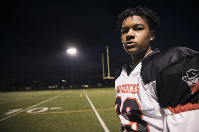 Portrait confident, tough teenage boy high school football player on football field at night