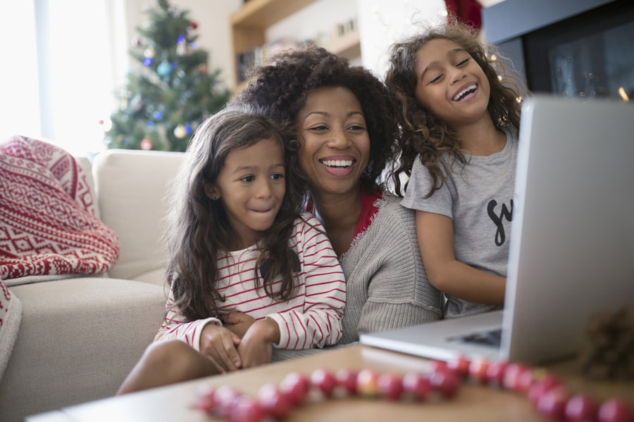 Laughing mother and daughters video chatting at laptop in Christmas living room by Hero Images Hero Images on 500px.com