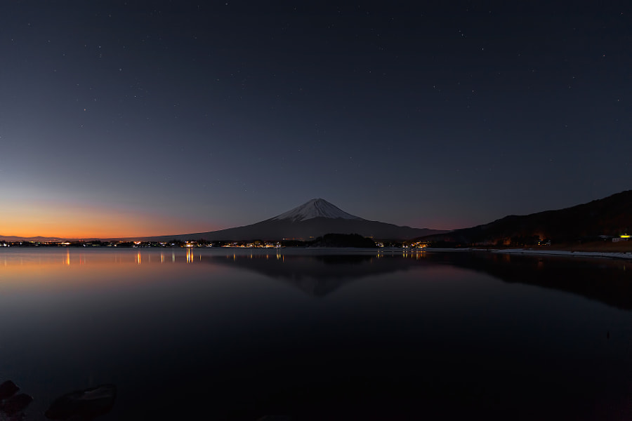 When lake surface is windless we can find an inverted image of Mt.Fuji reflected in the lake. This place is lake Kawaguchiko before sunrise. Mountain is Fuji. (taken at 5:58 AM)