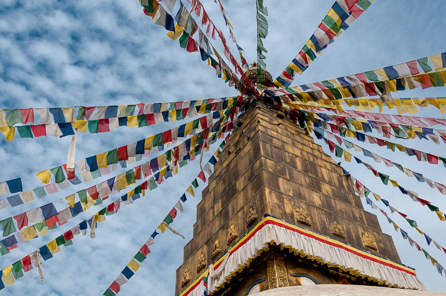 Prayer flags at the top of a stūpa by Patrick de Vries on 500px.com