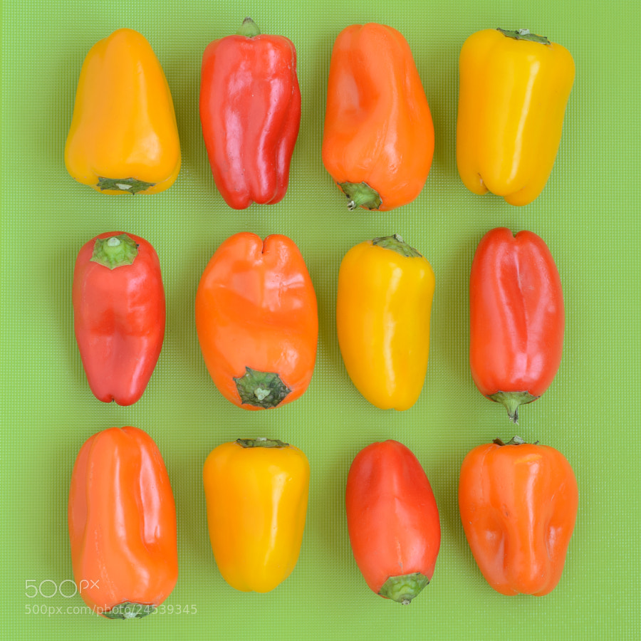 Red, orange, and yellow peppers on a green background