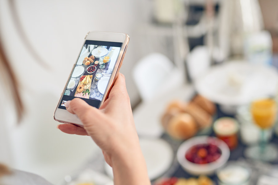 Woman taking a picture of her breakfast with her mobile phone by Lars Zahner on 500px.com