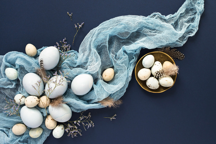 Easter background with blue painted eggs and napkin on dark blue by Olga Zarytska on 500px.com