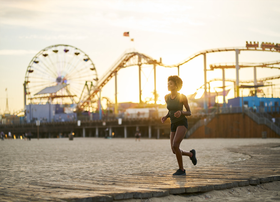 athletic african american woman jogging on boardwalk at sunset by Joshua Resnick on 500px.com