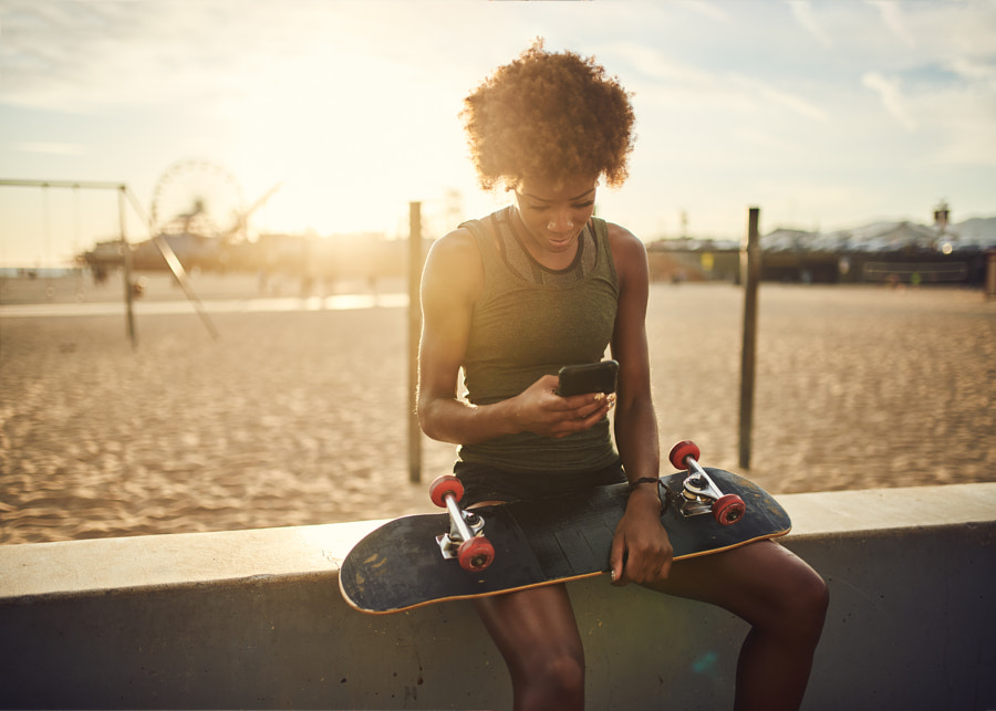 fit african american skater sitting down to look a by Joshua Resnick on 500px.com