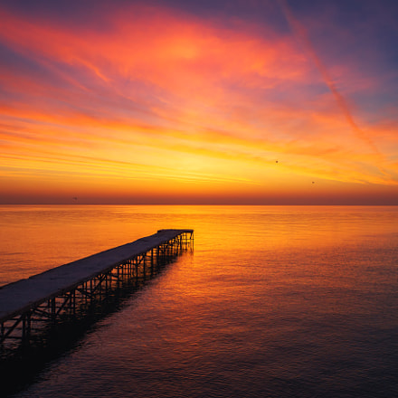 Aerial view over the old broken bridge in the sea, sunrise shot.