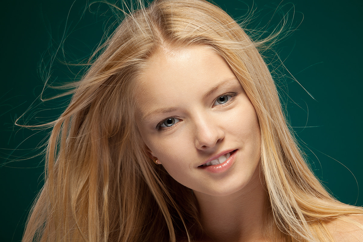 Photograph Close up portrait of smiling beautiful blond female with hair lightly fluttering in the wind by Pavel Kolotenko on 500px