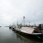 The Ku'ulakai (being restored) and fishing boats at the docks in Steveston BC, Canada, on a calm grey day.  A STORIED SHIP This 119-foot Mikimiki class ocean tug was originally named the Ernest F. Ladd, and was built in 1944 for the U.S. Navy by Northeast Shipbuilding Co. Quincy, Massachusetts, USA. It appears she was first used for towing disabled ships to port.   In 1949, Lloyd B. Gore added her to his Young & Gore Tugboat Co. fleet in British Columbia, and renamed her the Lloyd B. Gore.  She then she towed logs off the west coast for years. Court documents show that she did have a fishing license at one point, which a former owner had to forfeit when she was caught being used to smuggle drugs from Thailand. On appeal, however, the fishing license was reinstated.  She's now being restored by the current owner in Steveston BC.