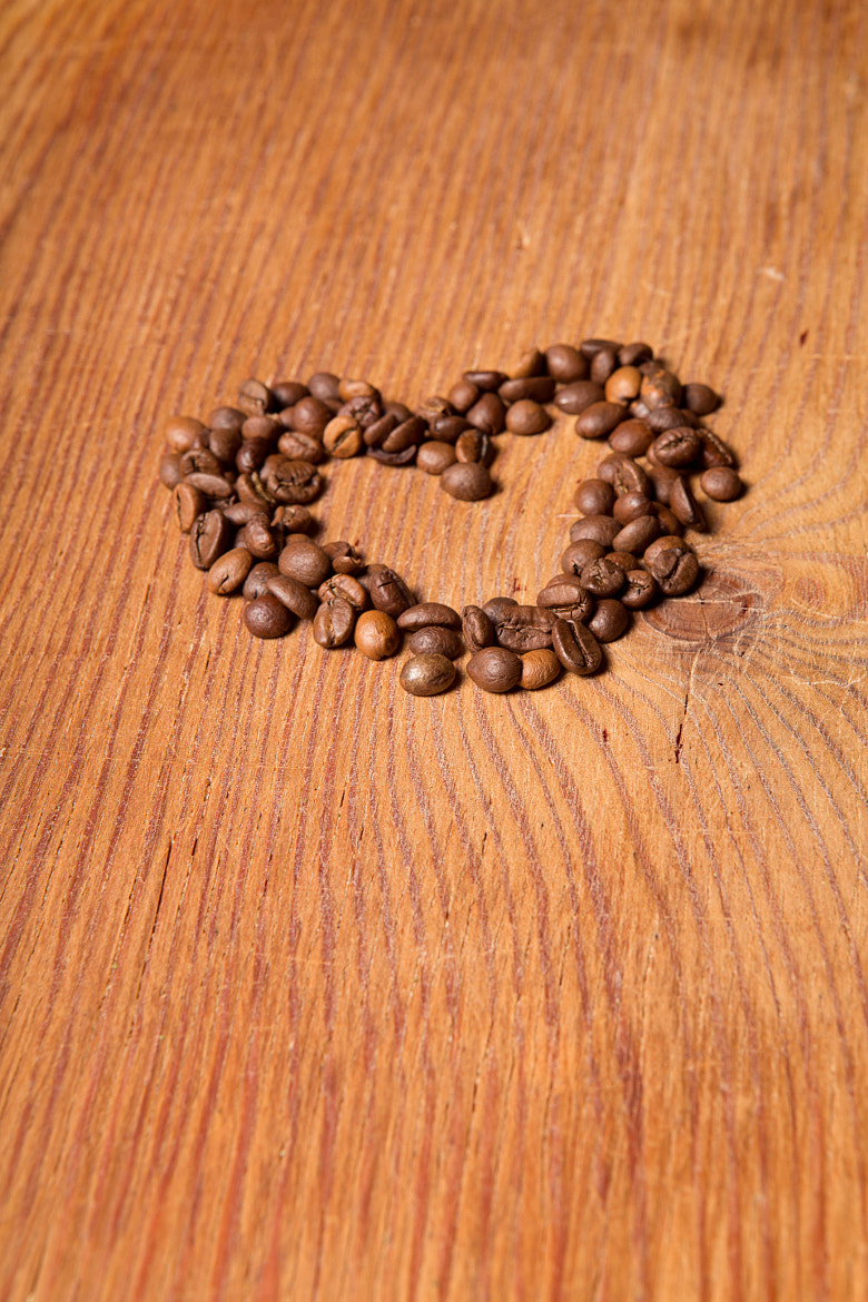 Photograph coffee beans in the form of heart on a wooden table by Ruslan Grigoriev on 500px