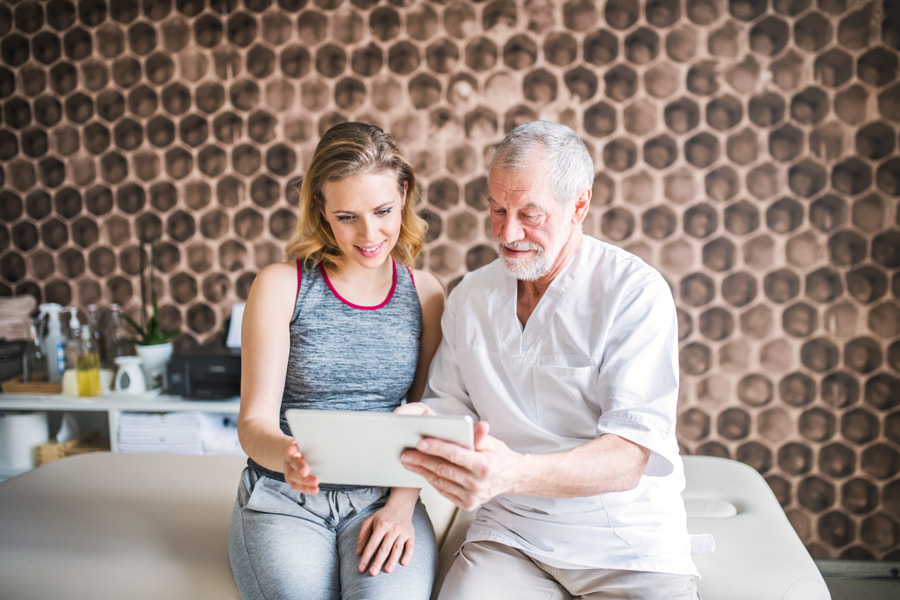 Senior male physiotherapist and young woman with tablet sitting. by Jozef Polc on 500px.com