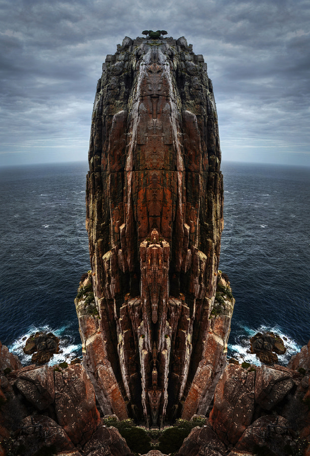 This image was taken at a remarkably scenic piece of coastline on the Tasman Peninsula, called Cape Hauy, here in Tasmania. There is a relatively short walk (just over an hour, from memory) over a recently upgraded track (part of the new Three Capes walk). Even without the mirroring the sea stack is pretty impressive, rising 122m out of the Great South Ocean. Most people look down on it from the top of the adjoining headland, but the intrepid can get a view from close to sea level by descending down a rock climbers track towards the aptly named Totem Pole (a 60m high sea stack that has a diametre of only 4m - impressive).