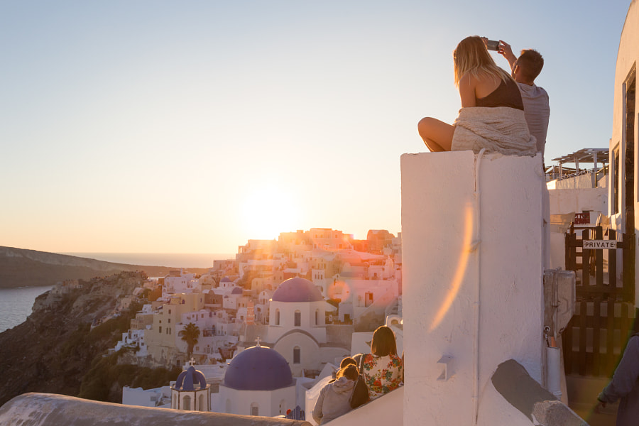 Couple watching sunrise and taking vacation photos at Santorini island, Greece. by Matej Kastelic on 500px.com