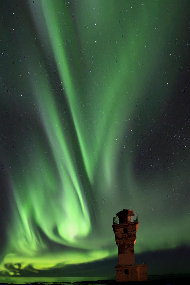 Photograph An old lighthouse and Northern lights by Jon Hilmarsson on 500px